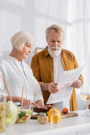 Elderly couple reading news while cooking on blurred foreground in kitchen