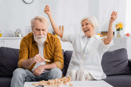 Excited senior woman looking at husband holding part of blocks wood game