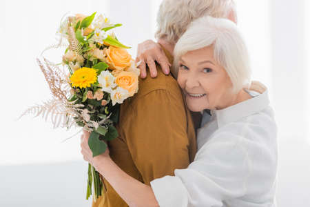 Smiling senior woman embracing husband and holding bouquet at home