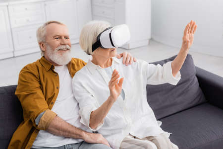 Senior man embracing wife in vr headset on sofa Banque d'images