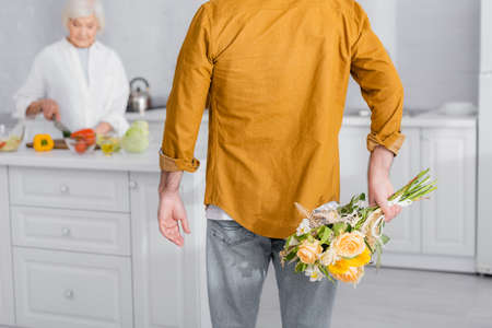 Senior man hiding flowers near wife cooking in kitchen on blurred background