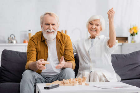 Elderly man holding block of wood tower game near wife showing yeah gesture Banque d'images