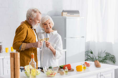 Smiling senior couple holding glasses of wine embracing near vegetables on blurred foreground