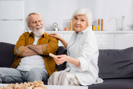 Senior woman holding part of blocks wood game near cheerful husband on couch