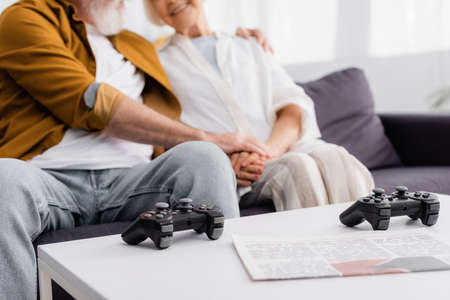 Cropped view of joysticks and newspaper on coffee table near senior couple on couch on blurred background