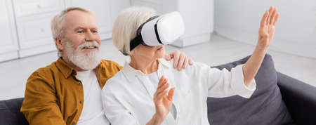 Smiling man hugging wife in vr headset on couch, banner