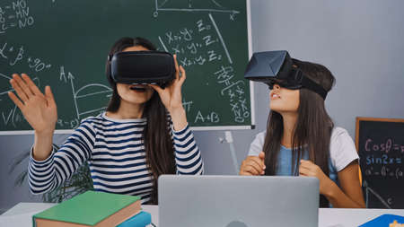 mother and daughter in vr headsets near laptop and books on desk