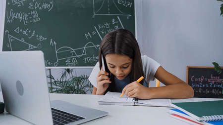 schoolkid talking on smartphone and writing in notebook near laptop on desk