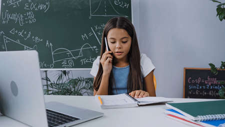 schoolgirl talking on smartphone and looking at notebook near laptop on desk