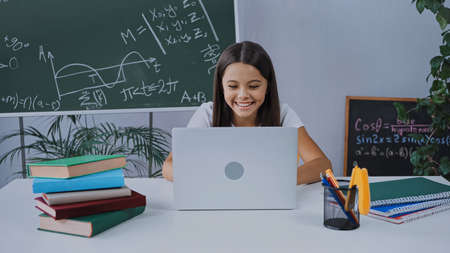 happy schoolgirl smiling while e-learning and looking at laptop