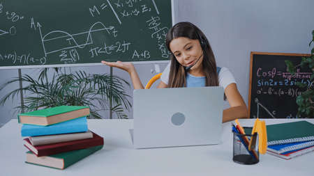 happy schoolkid in headset looking at laptop while pointing with hand at chalkboard
