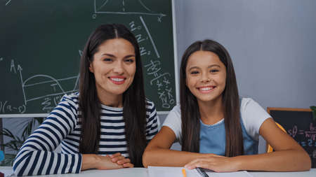 mother and daughter looking at camera and smiling near notebook at home