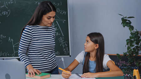 mother standing near upset daughter writing on notepad while doing homework