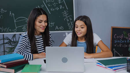 happy mother and daughter looking at laptop near notebooks on table