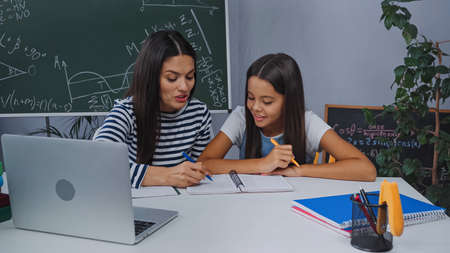 mother and happy daughter doing homework near laptop on desk