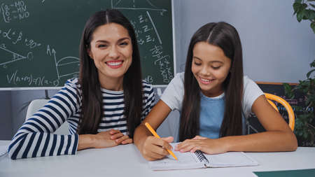 mother smiling near happy daughter doing homework at home