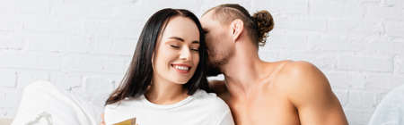 Muscular man kissing smiling woman in bedroom, banner
