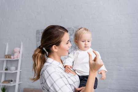 smiling mother showing small quantity gesture to toddler son