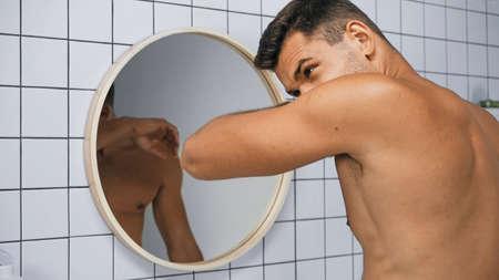 shirtless man smelling himself near mirror in bathroom