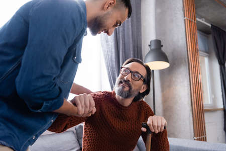 young hispanic man shaking hands with happy dad at home