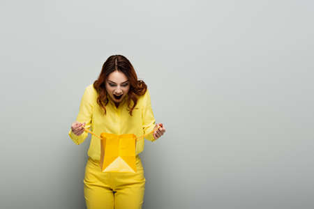 surprised woman in yellow clothes looking into shopping bag on gray