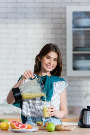 pleased woman pouring fresh smoothie near fruits on kitchen counter