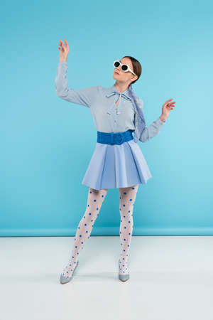 glamor woman in stylish clothes and sunglasses posing on blue background