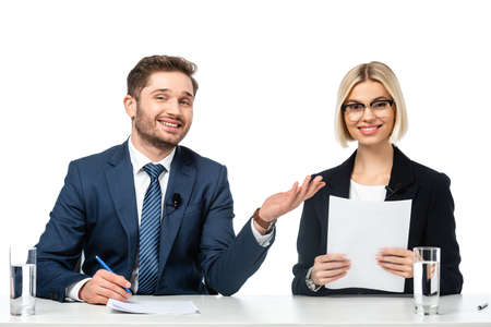 happy news anchor pointing at smiling colleague holding paper at workplace isolated on white