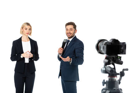 smiling broadcaster with microphone near blonde colleague and digital camera on blurred foreground isolated on white