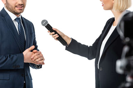 partial view of news presenter taking interview from businessman isolated on white, blurred foreground