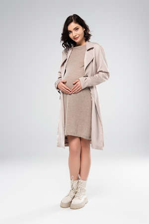 Brunette pregnant woman in coat looking at camera on gray background Banque d'images
