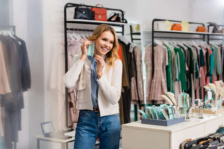 Cheerful woman holding earrings in showroom