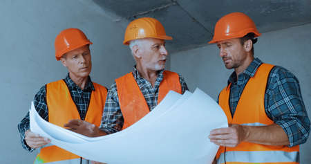 Builders in safety helmets talking while holding blueprints on construction site