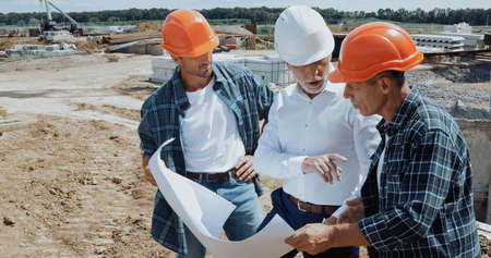 engineer and builders discussing blueprint on construction site