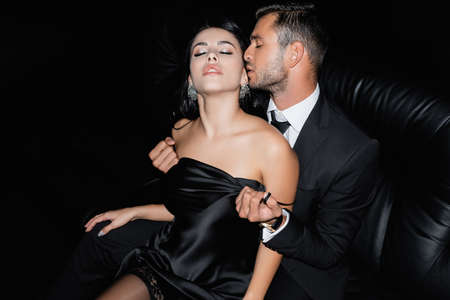 Sexy man taking off satin dress from girlfriend on couch isolated on black 版權商用圖片