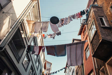 low angle view of clotheslines with laundry between houses on narrow street in Balat quarter, Istanbul, Turkey