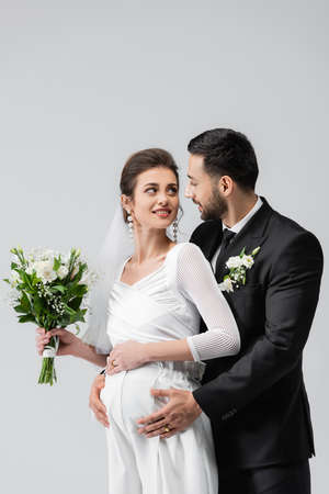 Pregnant bride looking at arabian groom in suit isolated on gray Standard-Bild