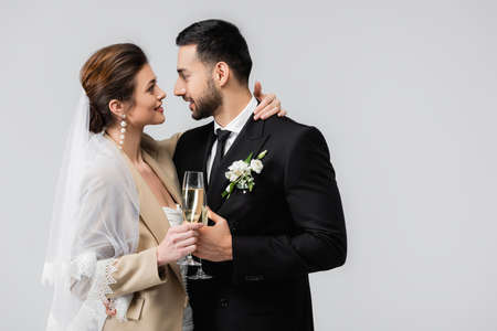 happy bride with champagne glass embracing neck of elegant arabian man isolated on gray Archivio Fotografico