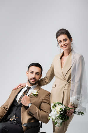 joyful woman with wedding bouquet touching shoulder of handicapped arabian fiance isolated on gray