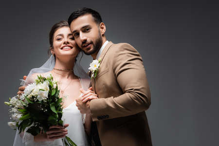 interracial newlywed couple smiling at camera isolated on gray