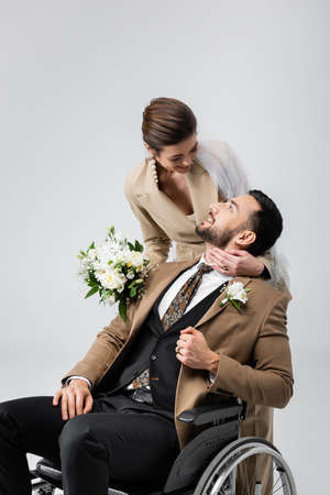 happy bride and disabled arabian man looking at each other isolated on gray Archivio Fotografico