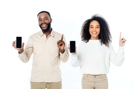 cheerful african american couple pointing up with fingers while showing smartphones with blank screen isolated on white