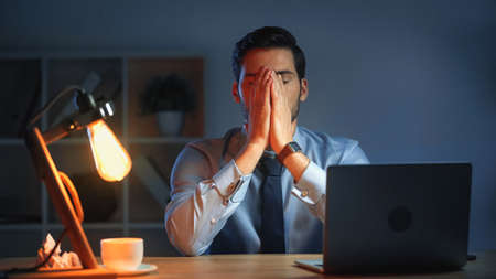 businessman covering face with hands while working late in office