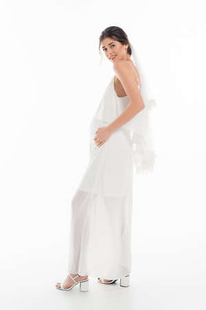 full length view of pregnant woman in wedding dress smiling at camera on white