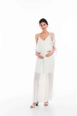 full length view of pregnant bride touching belly while looking at camera on white