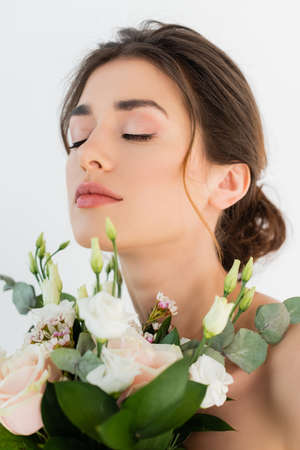young woman with wedding bouquet posing with closed eyes isolated on white
