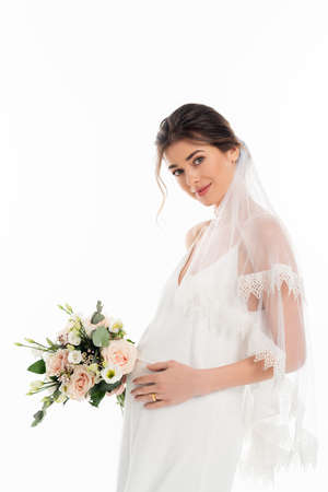 pregnant fiancee holding wedding bouquet while looking at camera isolated on white