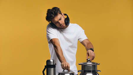 Man in headphones imitating playing music with pots and thermos isolated on yellow Stock Photo