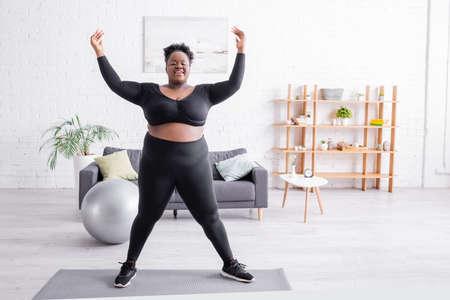 full length of cheerful african american plus size woman in sportswear training on fitness mat 版權商用圖片