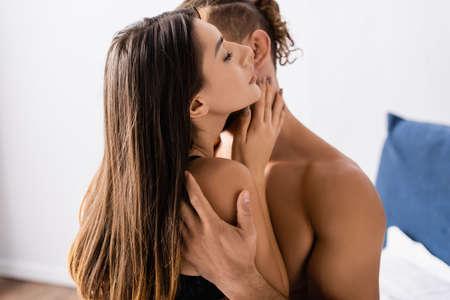 Brunette woman touching neck of shirtless boyfriend on blurred background